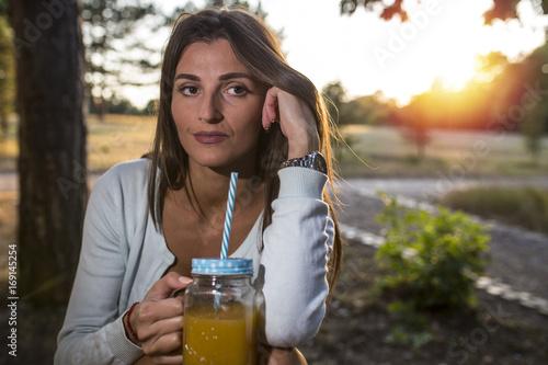 Woman drinks juice in a park