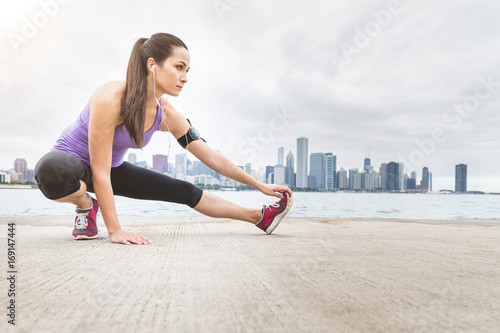 Woman doing stretching exercises with Chicago skyline on background