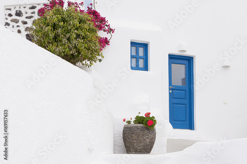 White house facade with blue door and flowers Santorini