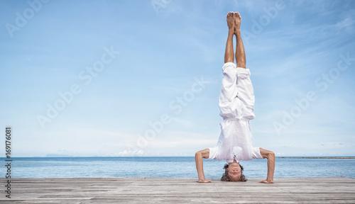 Obraz na płótnie Young man doing yoga exercise - headstand, on a beautiful tropical beach