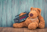 Retro Teddy Bear toy and old outdated ghetto blaster radio recorder from 80s front grunge wooden wall background. Listening rap music concept. Vintage instagram style filtered photo