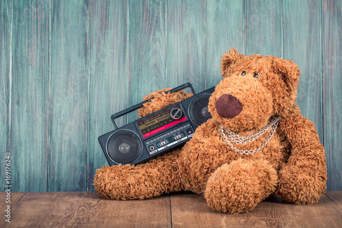 Retro Teddy Bear toy and old outdated ghetto blaster radio recorder from 80s front grunge wooden wall background Poster