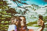 Happy man in 40s and daughter making selfie hiking mountain peak - 169176488