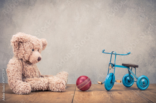 Retro Teddy Bear, old toy bicycle with three wheels and red leather ball. Vintage instagram style filtered photography