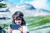 Happy young girl making selfie hiking mountain peak - 169177667