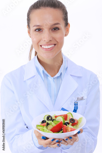 Portrait of a beautiful woman doctor holding a plate with fresh vegetables. Woman doctors.