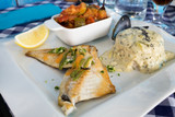 Grilled mediterranean fish fillets served with rice, vegetable ratatouille and mussels in the restaurant of Gruissan, France - 169183200