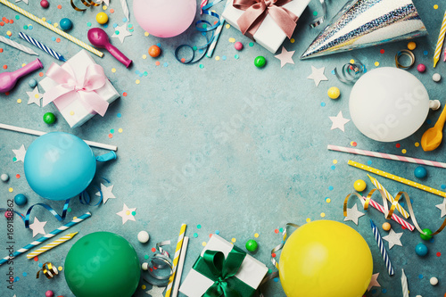 Holiday frame or background with colorful balloon, gift, confetti, silver star, carnival cap, candy and streamer. Flat lay style. Birthday or party greeting card with copy space.