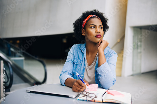 Young African female entrepreneur dreaming up new business ideas
