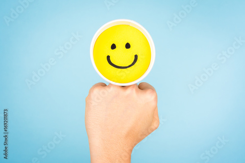 Happy face and woman making a fist on blue background. Poster