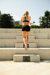 Quadro Young athletic woman exercising outdoors: running up the stairs