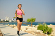 Quadro Young athletic woman exercising outdoors: running