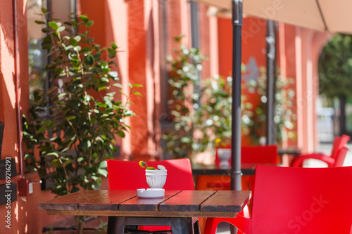 Fotobehang Pizzeria Outdoor restaurant with red tables and chairs