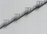 Stahltreppe nach oben an einer Blech verkleideten Wand - 169218270
