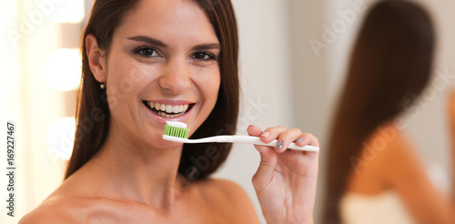 Portrait of a young girl cleaning her teeth Poster