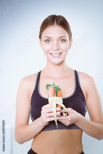 Woman holding a drinking glass full of fresh fruit salad with a tape measure around the glass.