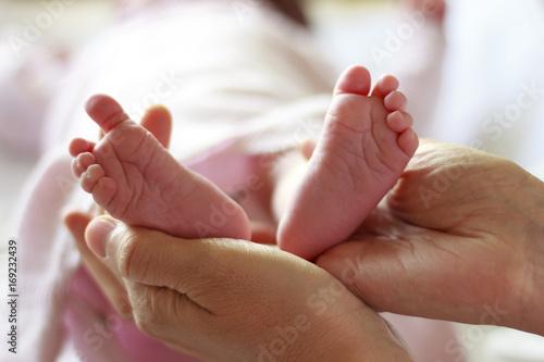 Pies de bebé recién nacido sobre las manos de su madre