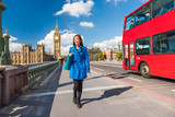 London Big Ben lifestyle tourist woman walking. Businesswoman going to work on Westminster bridge with red bus double decker background. Europe travel destination, England, Great Britain. - 169243619