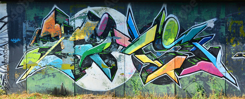 The old wall, painted in color graffiti drawing with aerosol paints. Background image on the theme of drawing graffiti and street art