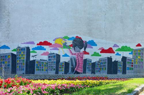 Stare ściany, malowane w kolorowy rysunek graffiti farbami w aerozolu. Obrazek mała dziewczynka która rysuje mnóstwo drapacze chmur z muśnięciem z farbami