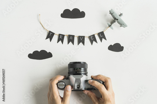 Retro camera with airplane toy on white background, Travel concept