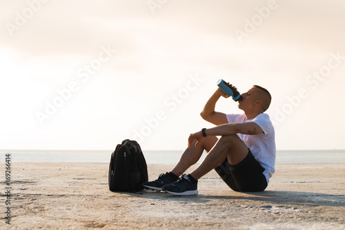 Tired young sportsman drinking water on ground