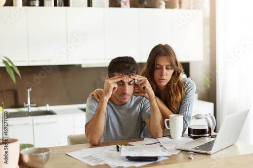 People, relationships, debts, financial stress and economic crisis. Unemployed young Caucasian man feeling depressed, sitting at kitchen table over unpaid bills while his wife trying to cheer him up