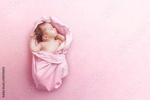 Newborn baby girl sleep on pink blanke