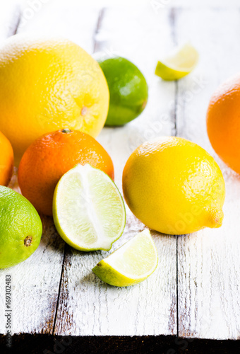 Poster Fresh citrus fruits on white rustic wooden background