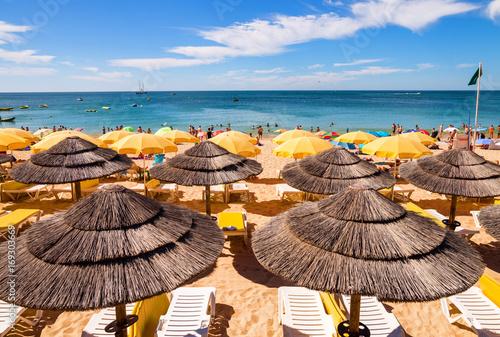 drapeau vert et parasols sur la plage Poster