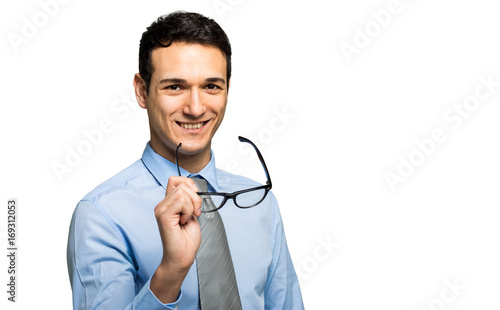 Young businessman holding a pair of eyeglasses
