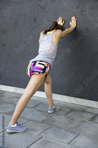 Pretty young woman stretching during exercise