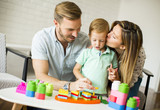 Little boy playing toys with mother and father at home