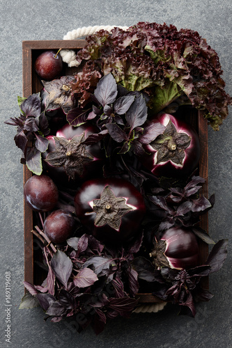 Wooden tray with purple vegetables and herbs on stone textured background