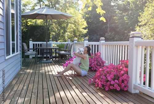 Woman hugging her dog while outdoors on home deck