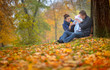 happy family walks in the autumn park, the father holds the kid on hands and considers the fallen-down leaves