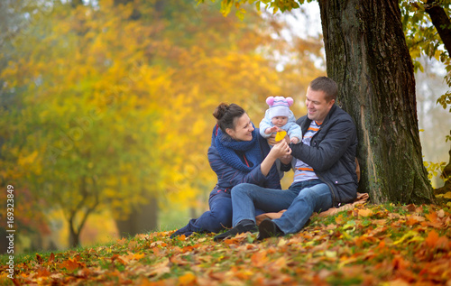 happy family walks in the autumn park, sit under a big tree and consider the fallen-down leaves