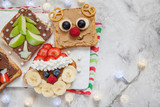 Funny Christmas faces toasts with banana, strawberry, raspberry and blueberry - 169330063