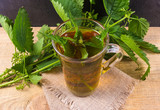 Healing tea with nettle. Tea in a glass cup on a wooden table. The source of vitamins. - 169338057