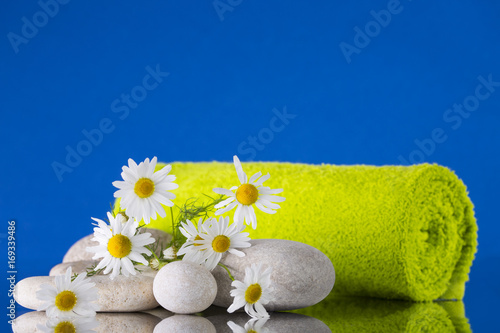 Fotobehang Spa Chamomile, pebbles, and a green towel on a blue background.