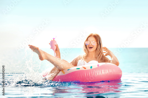 Aluminium Spa Summer Vacation. Woman in bikini on the inflatable donut mattress in the SPA swimming pool.