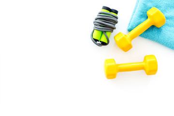 Fitness background. Jump rope, dumbbells on white background top view copyspace © 9dreamstudio