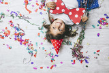 Little girl child cute and beautiful with multi-colored confetti on the floor and a festive hat happy happy bow