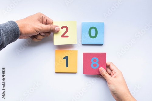 2018 text on colorful notepaper with human hand.business concepts