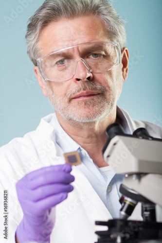 Portrait of senior life science research researching in modern scientific laboratory. Focused senior life science professional holding and observing the micro chip. Lens focus on scientists face.