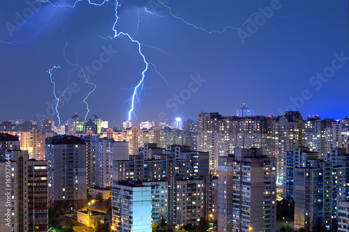 Large lightning bolts above the city. Poster