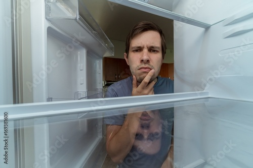 Hungry man is looking for food in empty fridge.