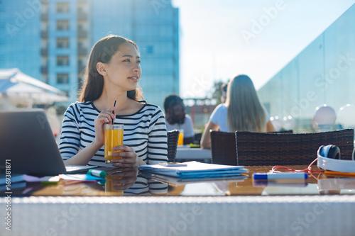 Dreaming freelancer drinking juice while working