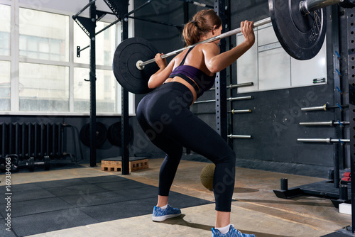 Poster Back view of  strong young woman lifting heavy barbell performing shoulder squat during intense workout in modern gym