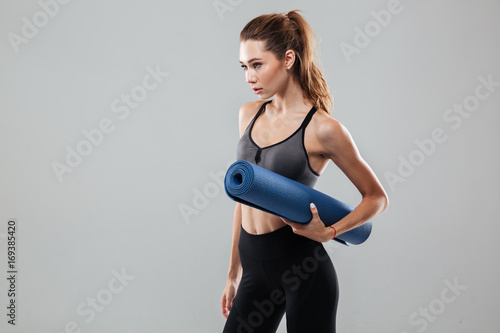 Confident young sportswoman holding fitness mat